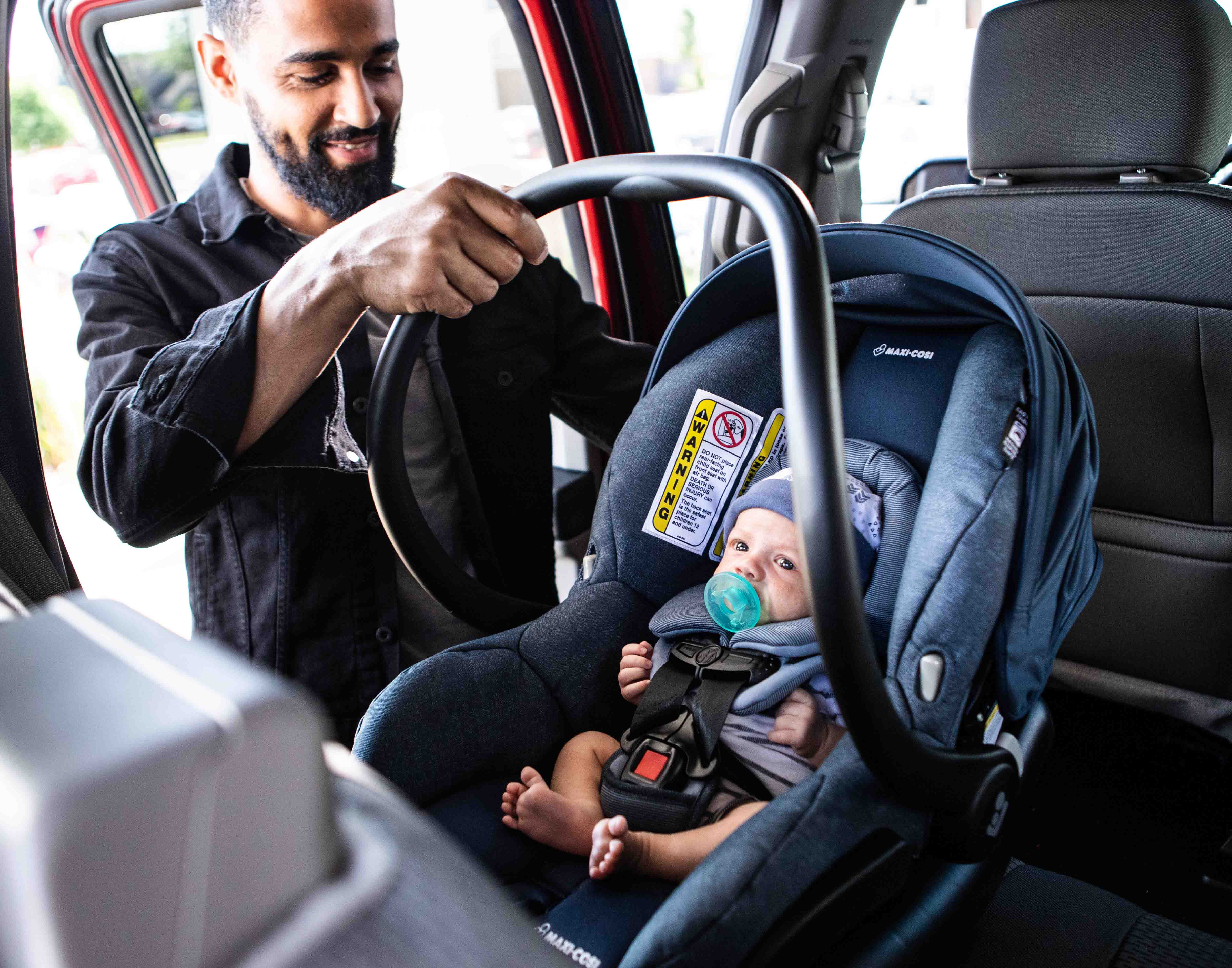 Dad placing infant car seat with baby in the car