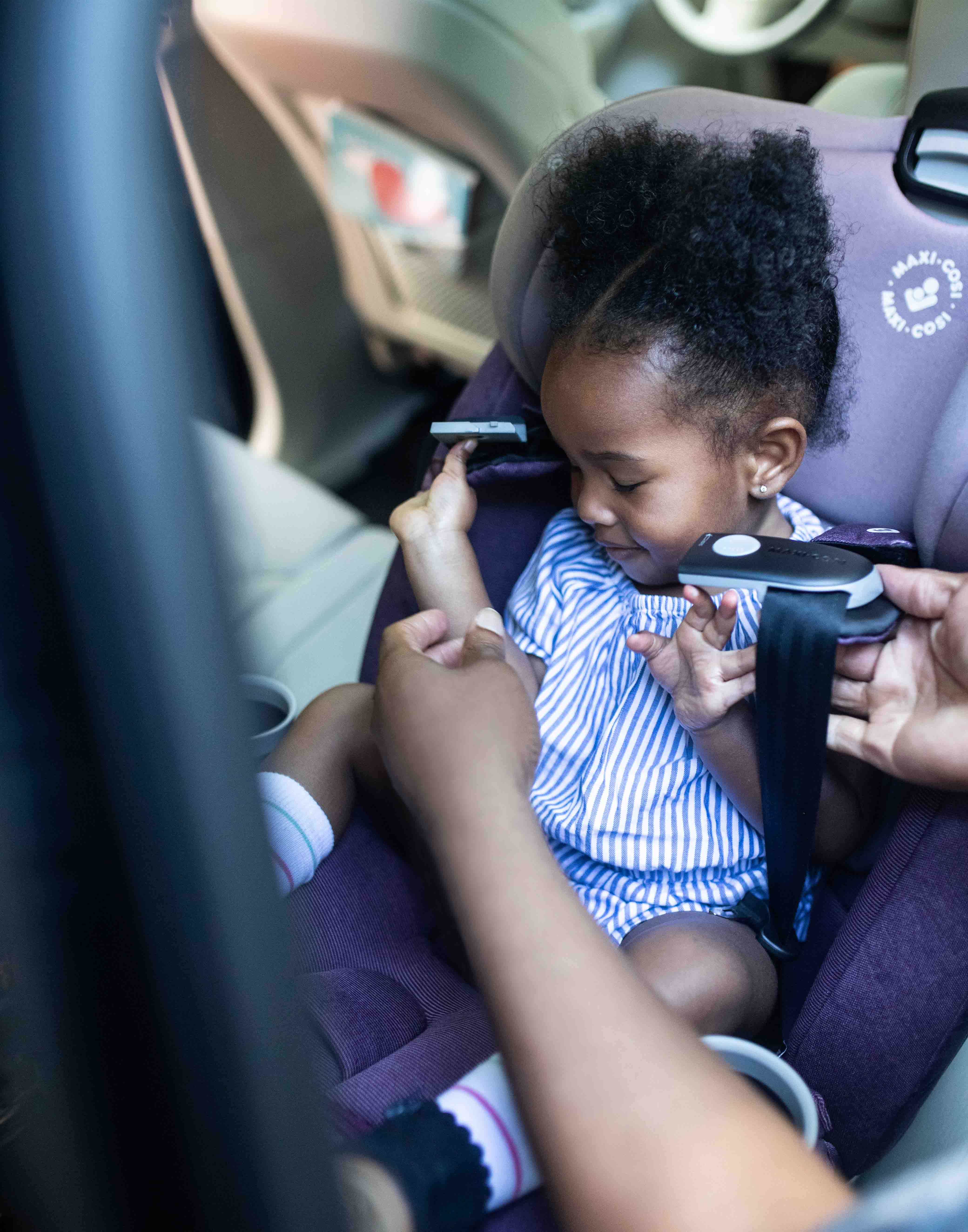 Little girl helping her parent buckle her into car seat